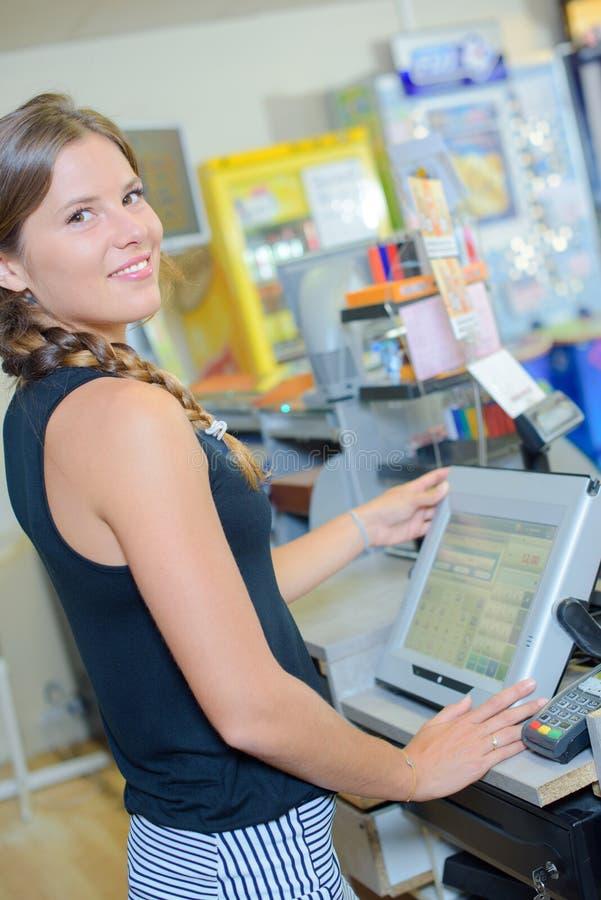 Junger weiblicher Kassierer, der am Bargeldschreibtisch im Speicher funktioniert stockbild