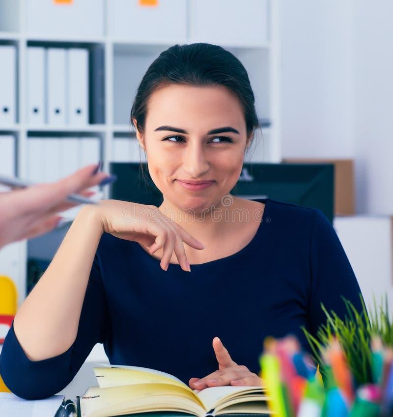 Junger weiblicher Kragen, der während der Sitzung im Bürokonferenzsaal lächelt Bunte Puppen auf schwarzem Hintergrund stockbild