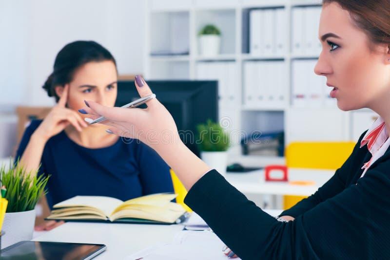 Junger weiblicher Kragen, der während der Sitzung im Bürokonferenzsaal lächelt Bunte Puppen auf schwarzem Hintergrund lizenzfreie stockfotografie