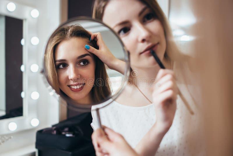 Junger weiblicher Kunde, der im Spiegel während Maskenbildner arbeitet an ihren Augenbrauen im Schönheitssalon schaut stockfotografie