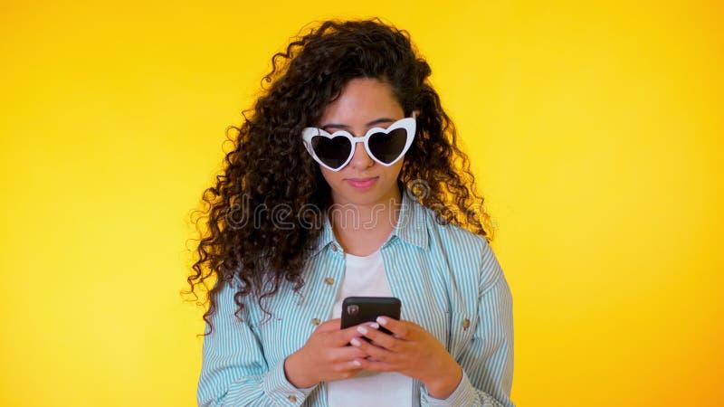 Junger weiblicher lächelnder und Anwendungshandy über gelbem Hintergrund Schönes Mischrassemädchen, das mit hält und simst lizenzfreies stockbild