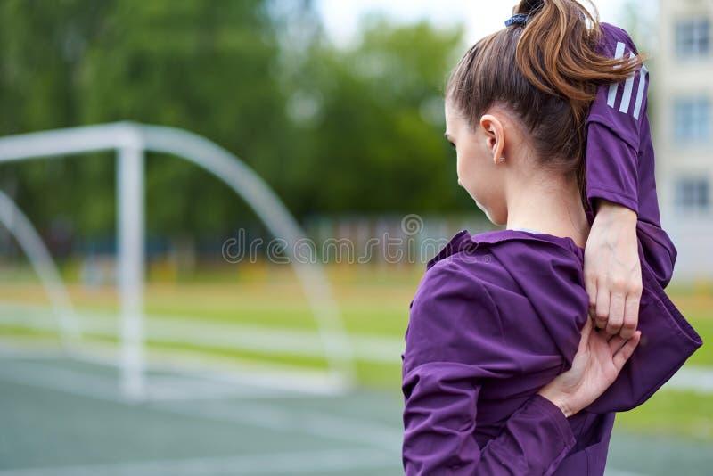Junger weiblicher Läufer, der Arme bevor dem Laufen ausdehnt lizenzfreies stockbild