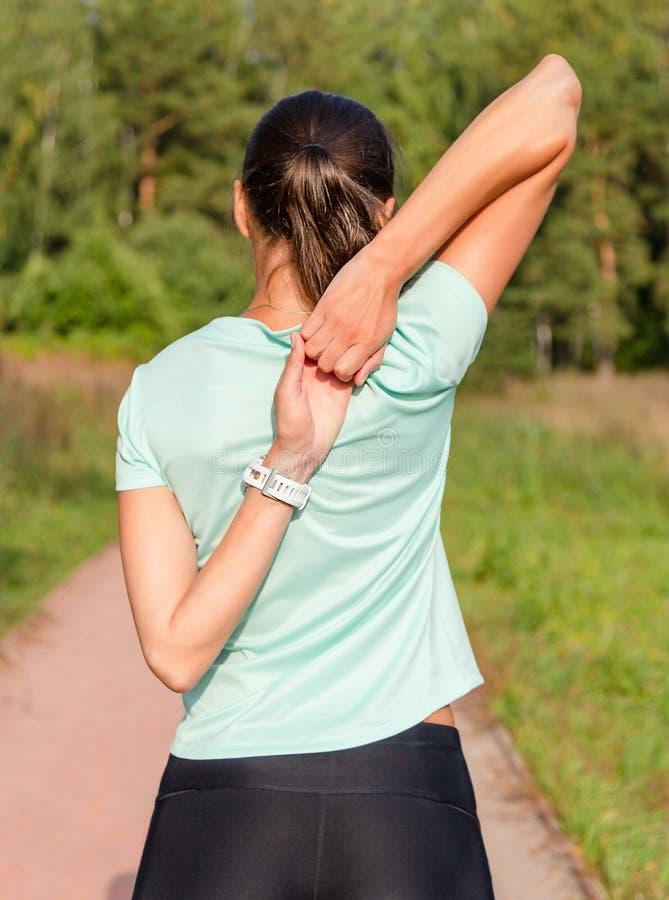 Junger weiblicher Läufer, der ihre Waffen vor Übung ausdehnt lizenzfreies stockfoto