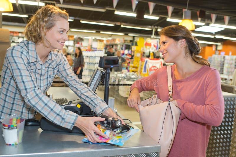 Junger weiblicher Ladenangestellterumhüllungskäufer am Bargeldschreibtisch lizenzfreies stockbild