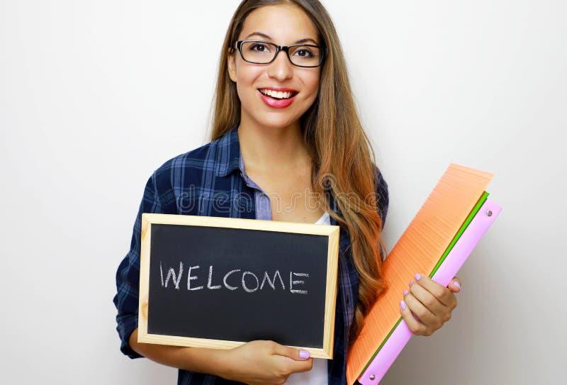 Junger weiblicher Lehrer, der Ordner und Tafel mit schriftlichem Willkommen hält stockfoto