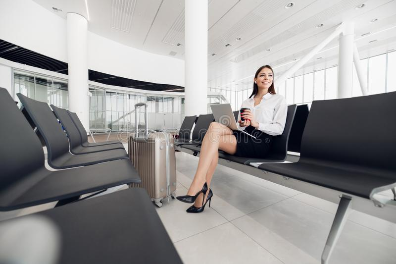 Junger weiblicher Passagier des Flughafens auf intelligentem Telefon und dem Laptop, die in der Terminalhalle beim Warten auf ihr lizenzfreie stockfotografie