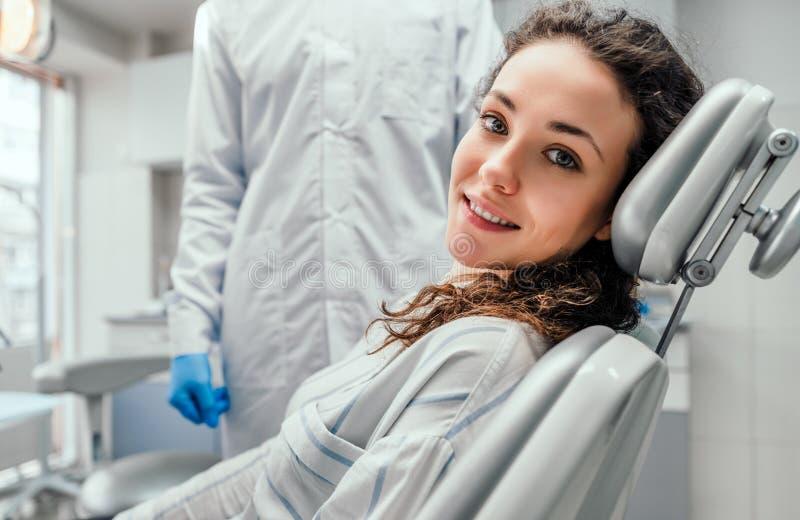 Junger weiblicher Patient, der auf Stuhl im zahnmedizinischen B?ro sitzt Vorbereiten f?r zahnmedizinische Pr?fung Betrachten der  lizenzfreie stockfotos