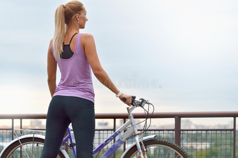 Junger weiblicher Radfahrer nahe bei ihrem Fahrrad, welches die Stadt betrachtet lizenzfreie stockbilder