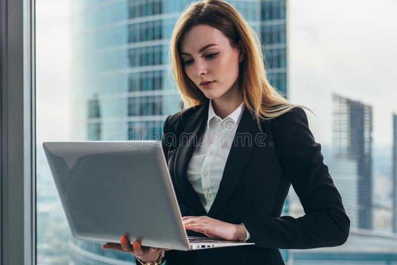 Junger weiblicher Rechtsanwalt, der in ihrem luxuriösen Büro hält einen Laptop an steht gegen panoramisches Fenster mit einer Ans stockfotografie