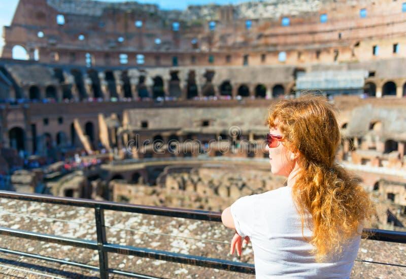 Junger weiblicher Rothaarigetourist betrachtet das Colosseum in Rom stockbild