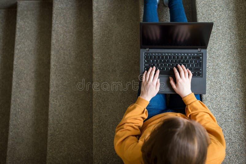 Junger weiblicher Student, der in der Schule auf Treppe, Versuch auf ihren Laptop schreibend sitzt getrennte alte Bücher stockfotografie