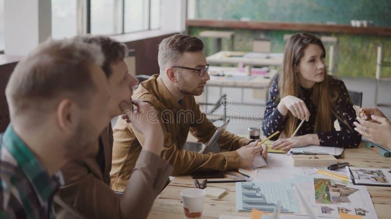 Junger weiblicher Teamleiter, der mit kleiner gemischtrassiger Gruppe von Personen spricht Geschäftstreffen des Jungunternehmens  lizenzfreies stockbild