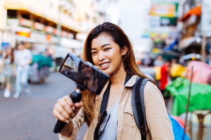 Junger weiblicher Tourist, der einen Kardanring mit Smartphone h?lt und Videos notiert Reise Blogger- und vloggerkonzept lizenzfreie stockfotos