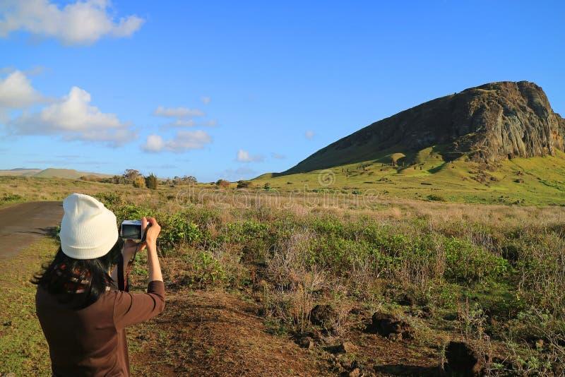 Junger weiblicher Tourist, der Fotos von Rano Raraku-Vulkan, Steinbruch von Moai-Statue in der alten Zeit von Osterinsel macht lizenzfreie stockfotos