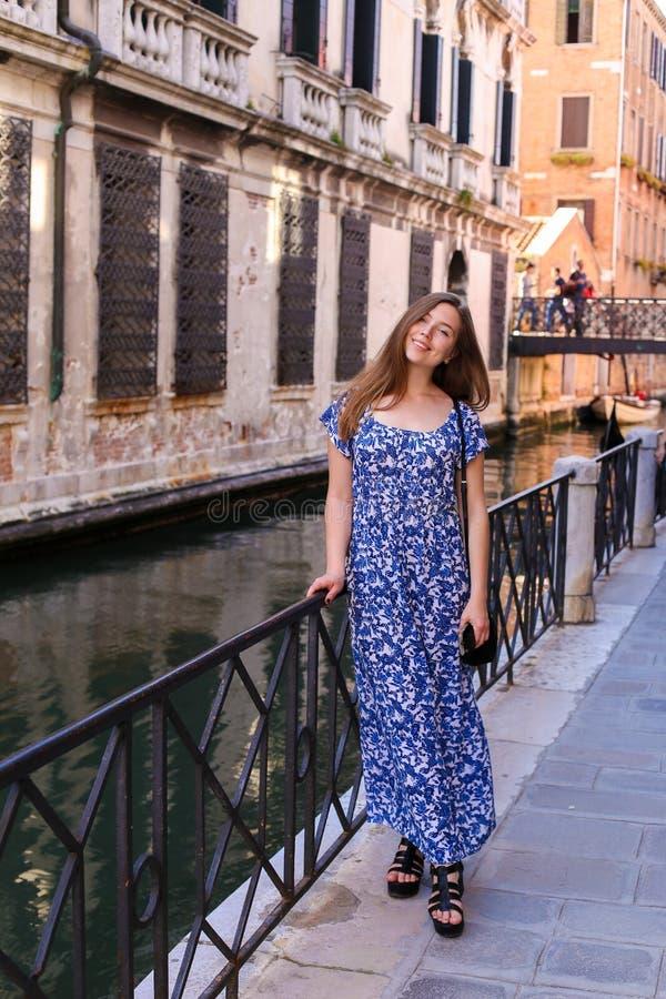 Junger weiblicher Tourist, der nahe Geländerdocke in Venedig, Italien steht stockfotografie