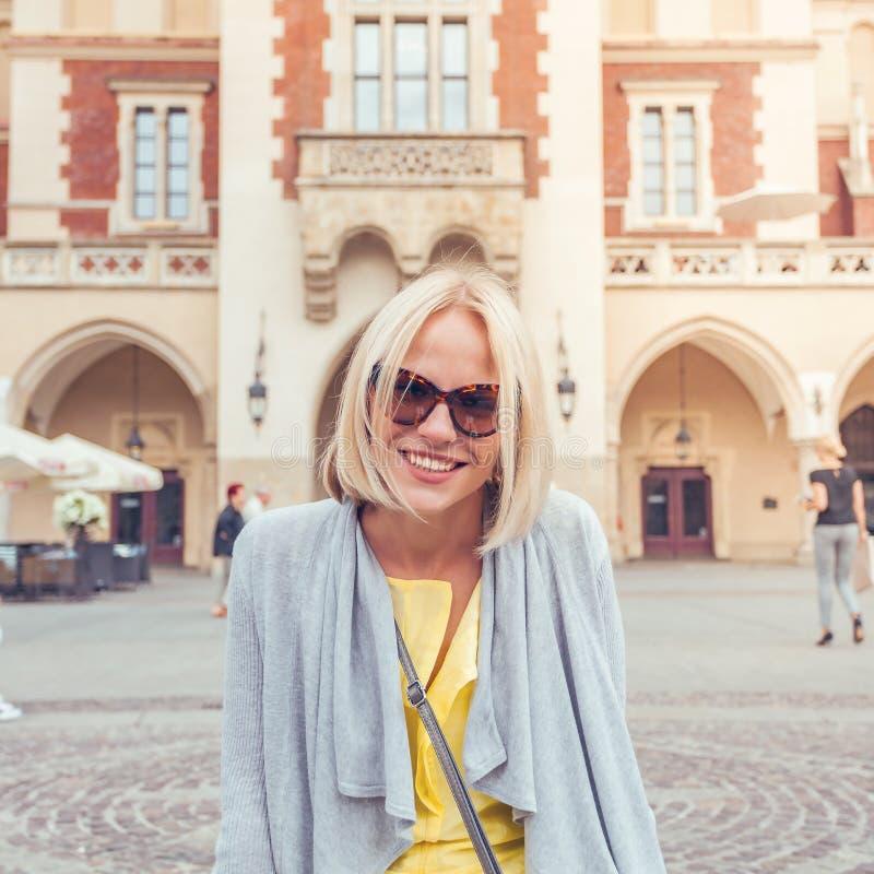Junger weiblicher Tourist, der nahe Stoff Hall im alten Stadtzentrum von Krakau sitzt lizenzfreies stockbild