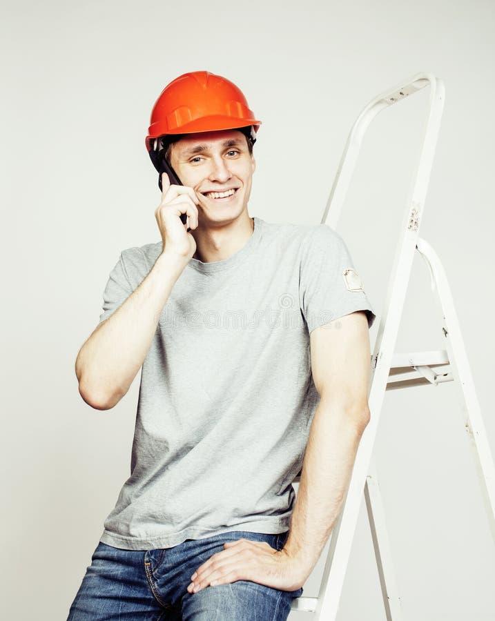 Junger wirklicher Arbeitsmenschmann lokalisiert auf weißem Hintergrund auf der lächelnden Aufstellung der Leiter, Geschäftskonzep lizenzfreie stockfotos
