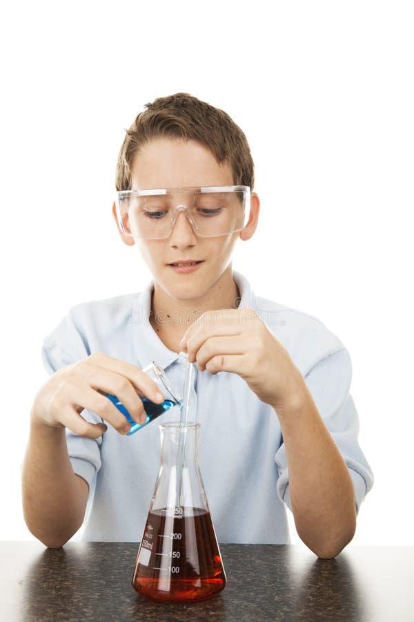 Junger Wissenschaftler mischt Chemikalien lizenzfreie stockfotos