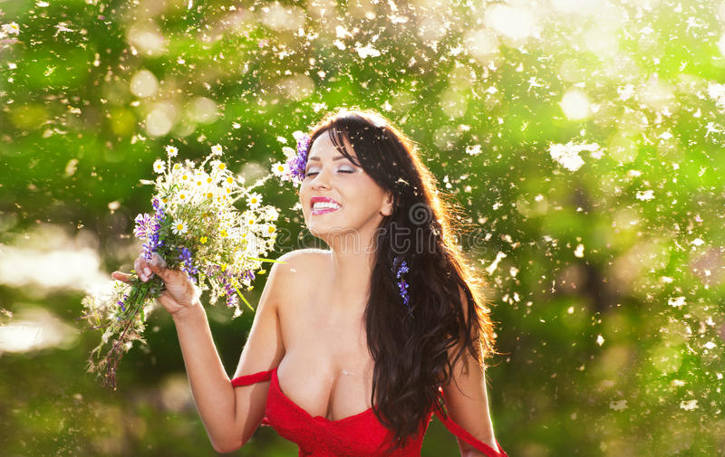 Junger wollüstiger Brunette, der einen Blumenstrauß der wilden Blumen an einem sonnigen Tag hält Porträt der Schönheit mit tief a lizenzfreies stockbild