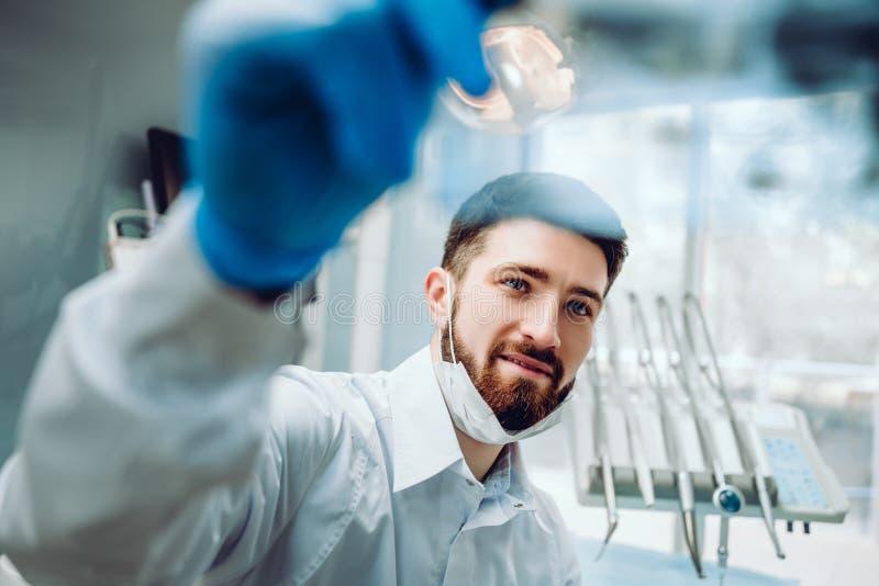 Junger Zahnarzt, der einen Film des Strahls x auf dem Hintergrund im zahnmedizinischen Büro konsultiert lizenzfreie stockfotografie