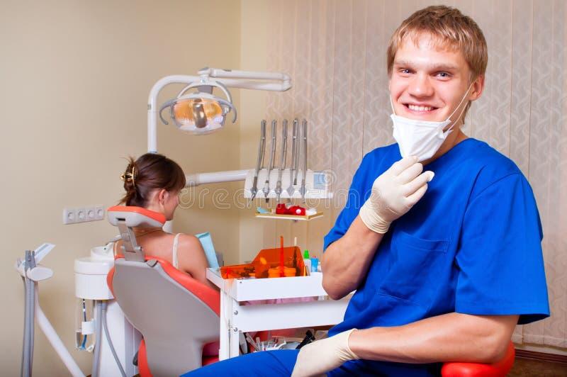 Junger Zahnarzt in seinem Büro, das den Projektor betrachtet lizenzfreies stockfoto