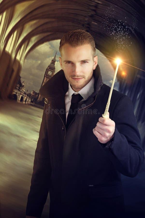 Junger Zauberer, der einen magischen Stab hält stockfotos