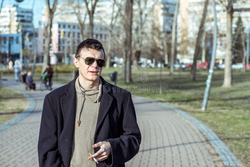 Junger zufälliger Rauchermann mit Sonnenbrille in der rauchenden Zigarette des schwarzen Mantels draußen im Park lizenzfreies stockbild