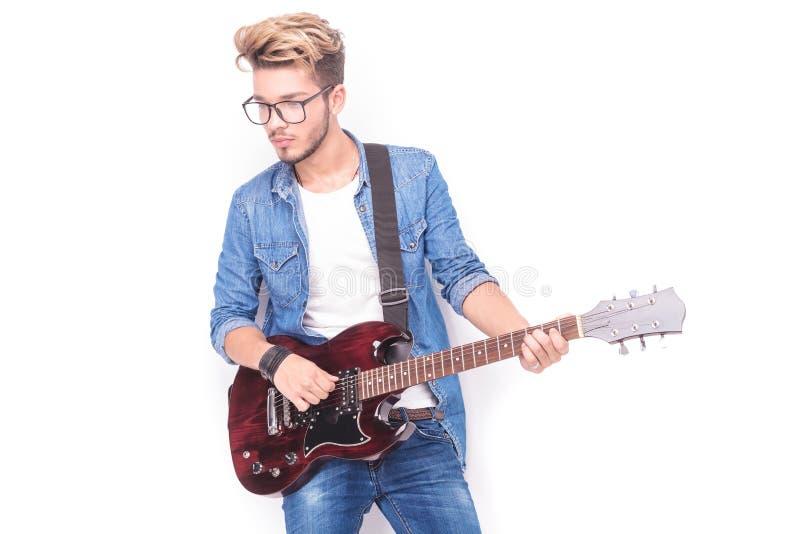 Junger zufälliger Gitarrist, der seine E-Gitarre und Blicke awa spielt stockfotografie