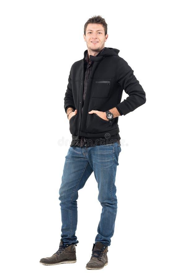 Junger zufälliger lächelnder Mann in der mit Kapuze Winterjacke mit den Händen in den Taschen stockfotos