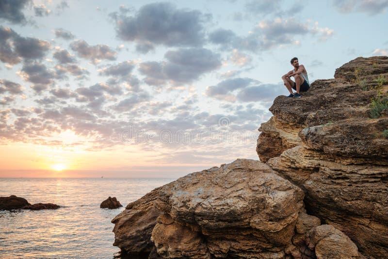 Junger zufälliger Mann, der auf dem Gebirgsfelsen sitzt lizenzfreie stockbilder