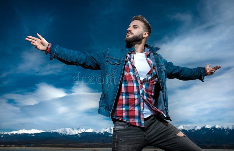 Junger zufälliger Mann, der bei der Atmung der Frischluft der Berge stark sich fühlt lizenzfreie stockbilder