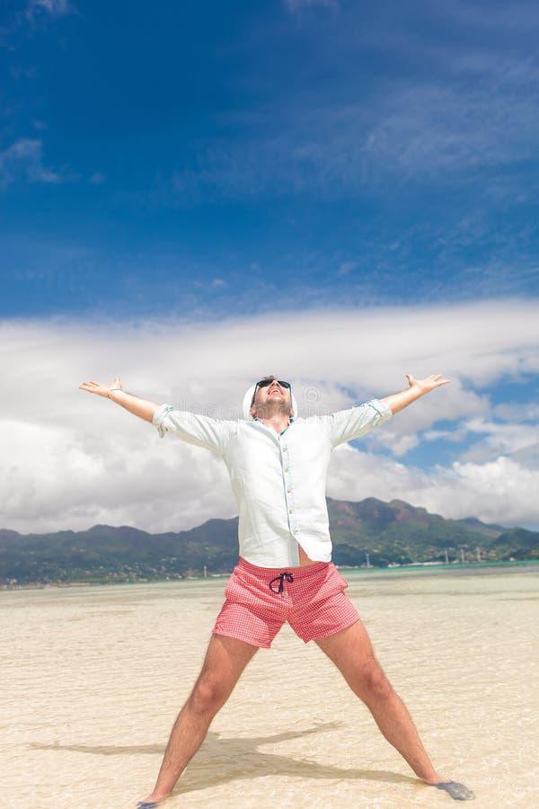Junger zufälliger Mann, der das Leben auf Strand feiert stockfoto