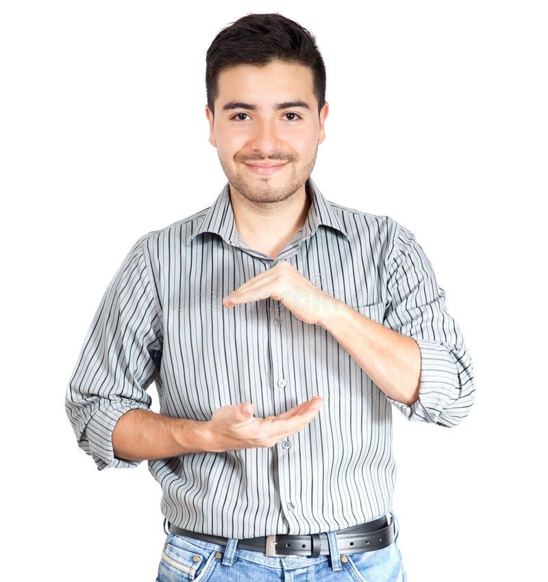 Junger zufälliger Mann, der etwas auf Händen am weißen Hintergrund hält lizenzfreie stockfotos