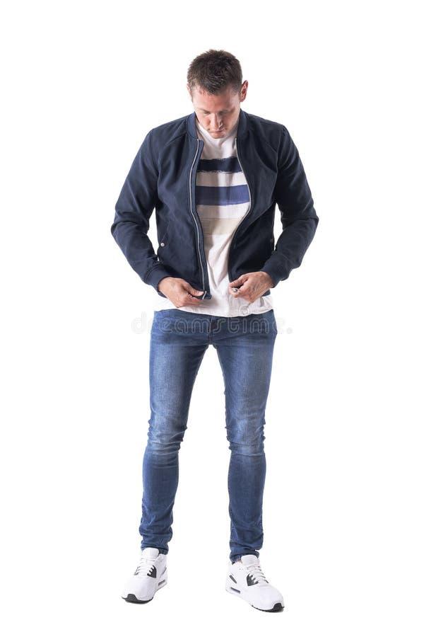 Junger zufälliger Mann, der gekleidetes und sich vorbereiten, Jackenerhält Befestiger oben Reißverschluss zuzumachen hochhalten lizenzfreie stockfotografie
