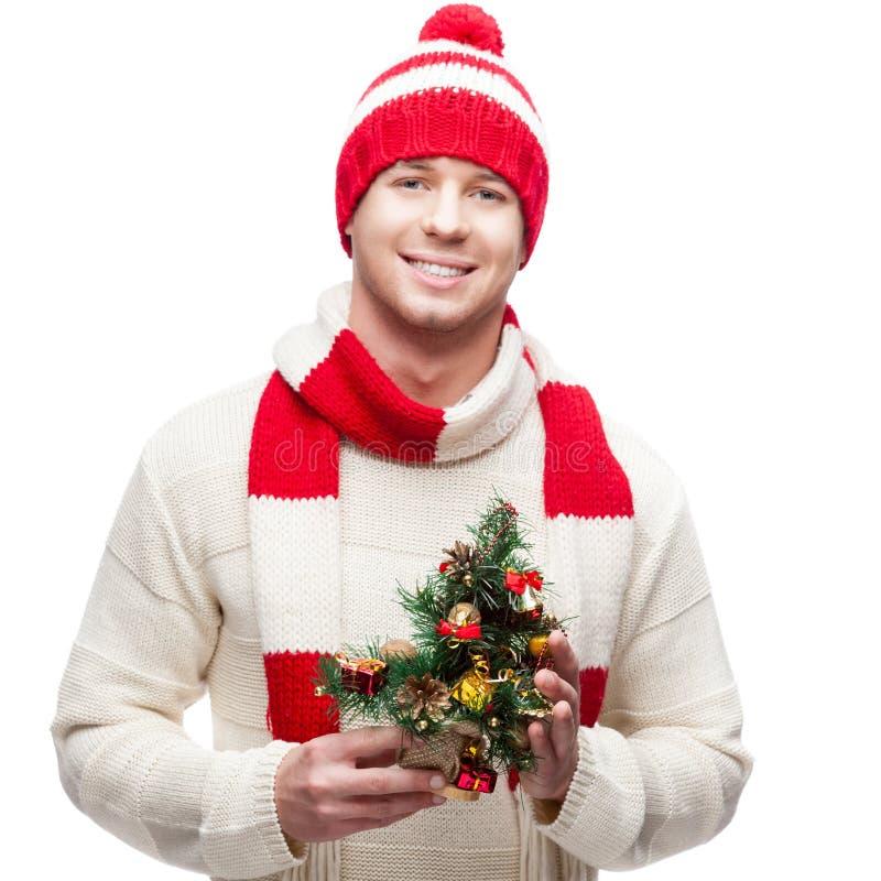 Junger zufälliger Mann in hoding Weihnachtsbaum des Winterhutes lizenzfreies stockfoto