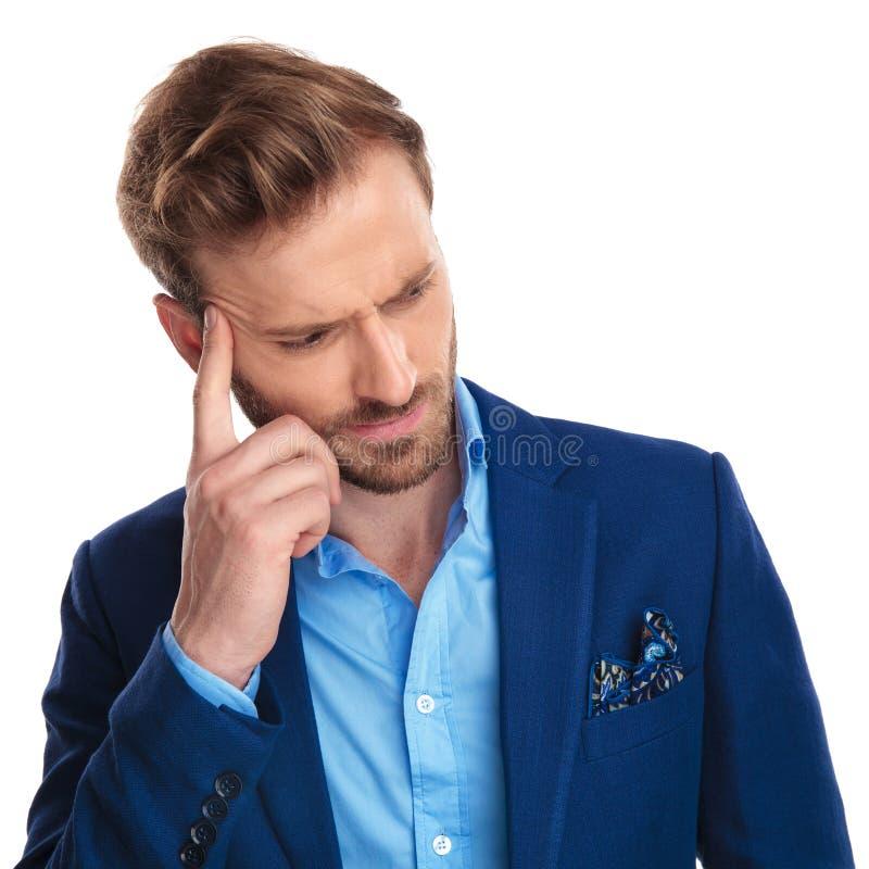 Junger zufälliger Mann mit dem Finger auf der Stirn, die Kopfschmerzen hat stockfotos