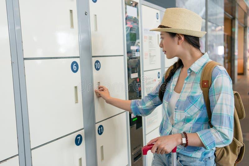 Jungereisefrau, die das Schließfach verwendet lizenzfreie stockbilder