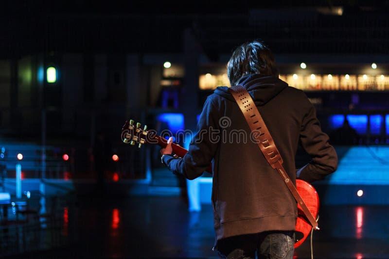 Jungerockmusiker auf dem Stadium, das Gitarre spielt lizenzfreie stockbilder