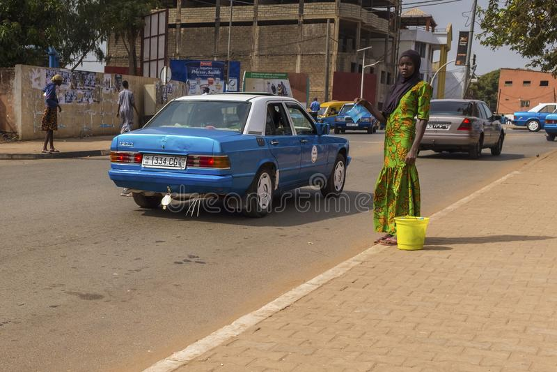 Junges afrikanisches Mädchen, das ein hijab verkauft Wasser in den Plastiktaschen nahe dem Bandim-Markt in der Stadt von Bissau t stockbild