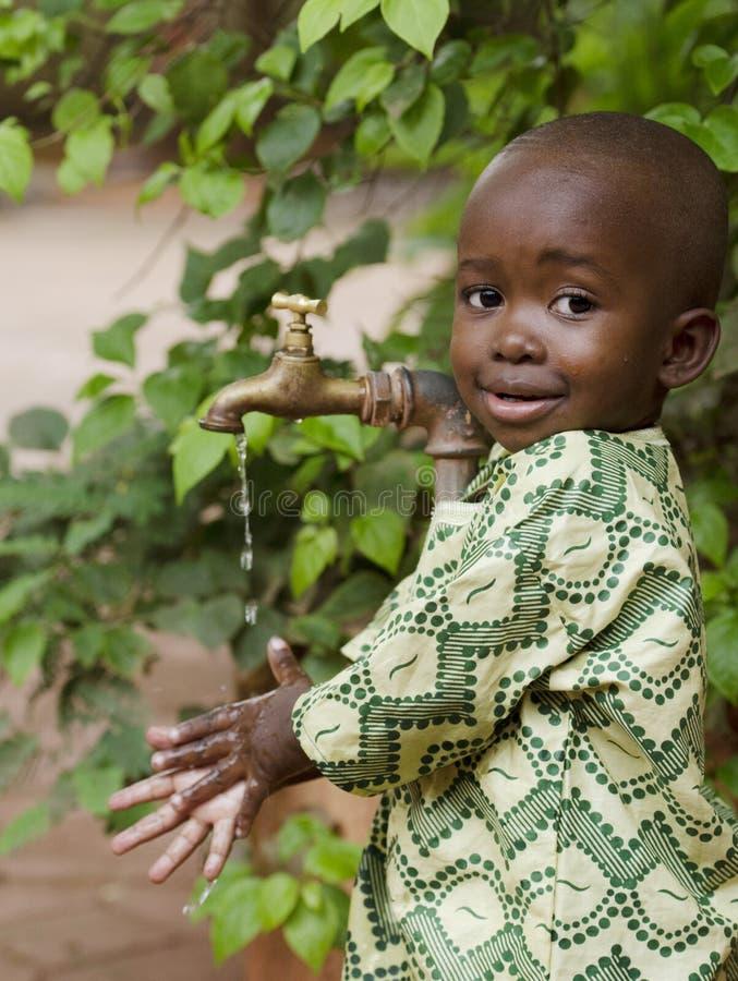 Junges afrikanisches Schuljungenhändchenhalten unter einem Hahn Wasser scarci stockbild