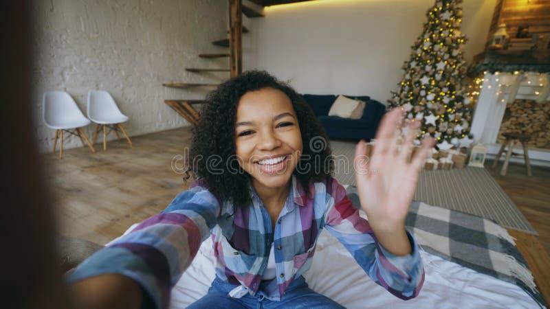 Junges Afroamerikanermädchen, das zu Hause on-line-Gespräch unter Verwendung der Smartphonekamera auf Weihnachten plaudert stockfoto