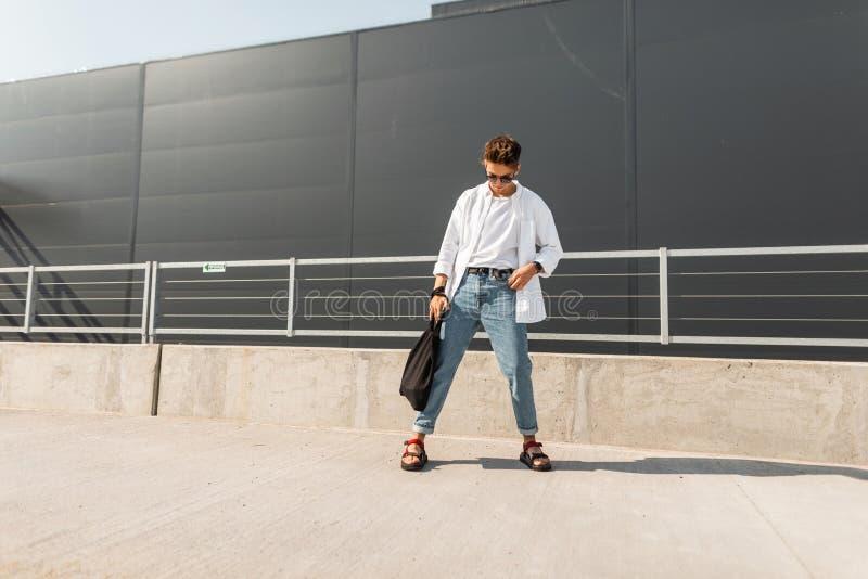Junges amerikanisches Mannmodell in einem weißen Hemd in den blauen stilvollen Jeans in der Sonnenbrille mit einer schwarzen Tasc stockfoto