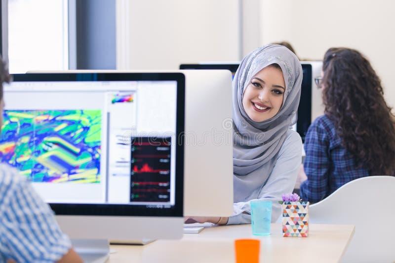 Junges arabisches Geschäftsfrau tragendes hijab, arbeitend in ihrem Start stockfotografie