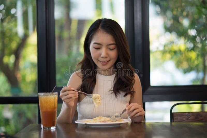 Junges Asiatinessenspaghettis carbonara lizenzfreie stockbilder