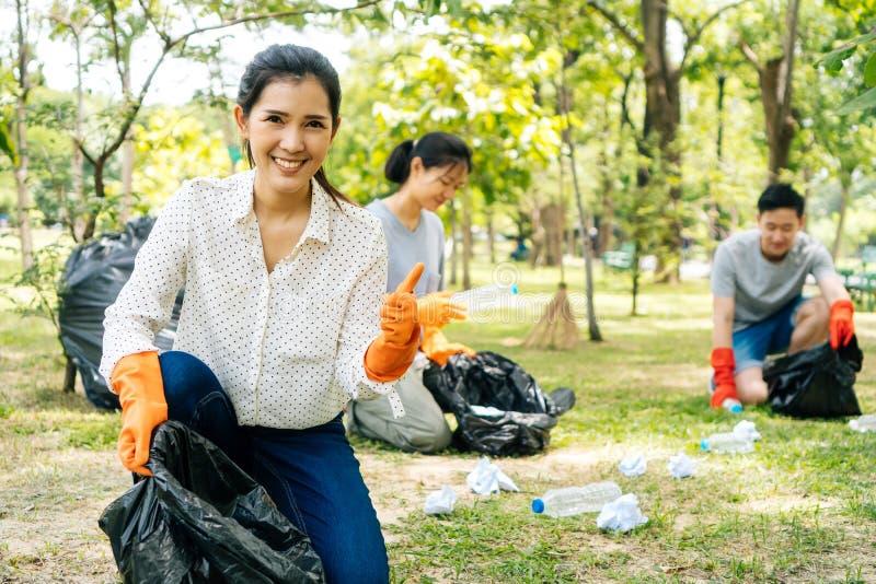 Junges Asiatinlächeln, Daumen mit den Freunden aufgebend, die Abfall in der Abfalltasche im Park sammeln lizenzfreie stockfotografie
