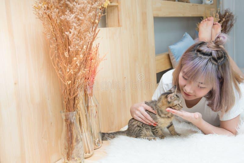 Junges asiatisches Damenspiel mit Katze auf Bett, Weinleseart lizenzfreie stockfotografie