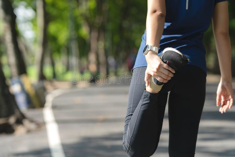 Junges asiatisches Frauenaufwärmen vor Training oder nachdem dem Laufen in allgemeinen Stadtpark der Natur unten abkühlen Herz Sp stockfoto