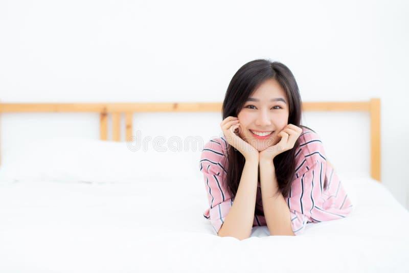 Junges asiatisches Frauenlügen und -lächeln des schönen Porträts, während mit Sonnenaufgang am guten Morgen aufwachen Sie stockfotos