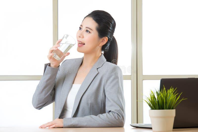 Junges asiatisches Geschäftsfrautrinkglas Wasser stockbild