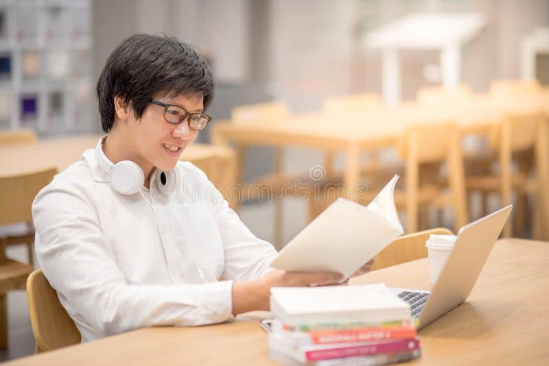 Junges asiatisches Hochschulstudentlesebuch in der Bibliothek stockbilder